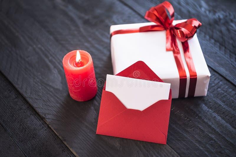 Letra en un regalo y una luz de una vela fotos de archivo libres de regalías
