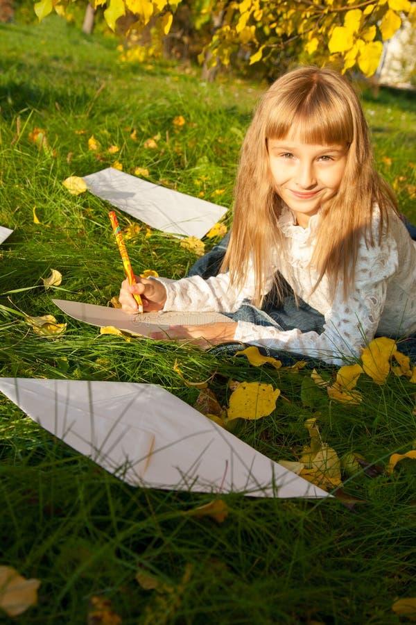 Letra hermosa de la lectura de la muchacha mientras que se sienta encendido fotos de archivo libres de regalías