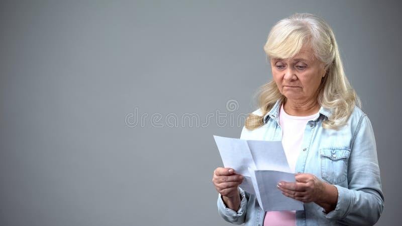 Letra idosa infeliz da leitura da mulher, recebendo más notícias, resultados da análise da saúde fotografia de stock royalty free