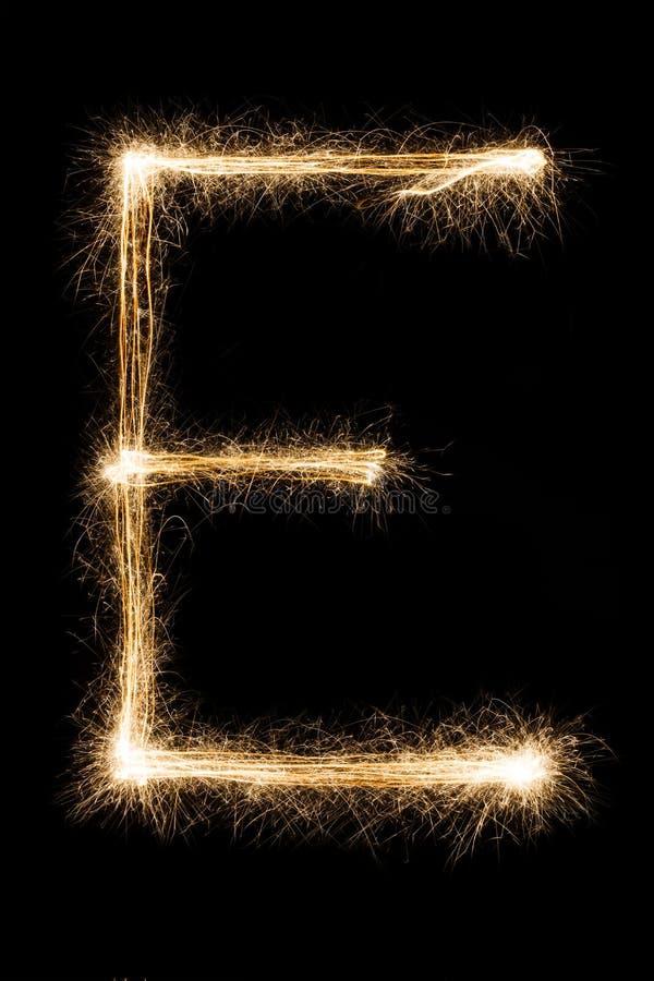 Letra inglesa E del alfabeto de las bengalas en fondo negro fotos de archivo