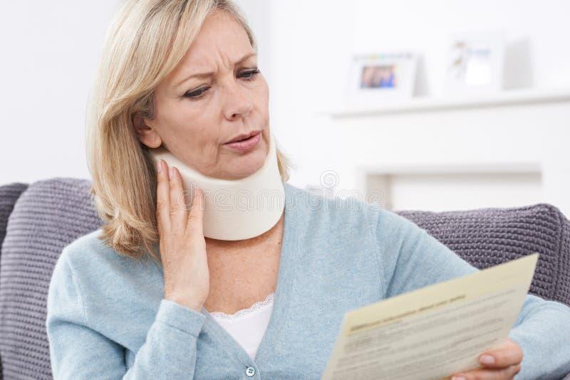 Letra madura da leitura da mulher após ter recebido ferimento do pescoço fotografia de stock