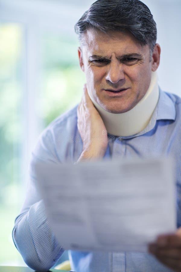 Letra madura da leitura do homem após ter recebido ferimento do pescoço fotos de stock