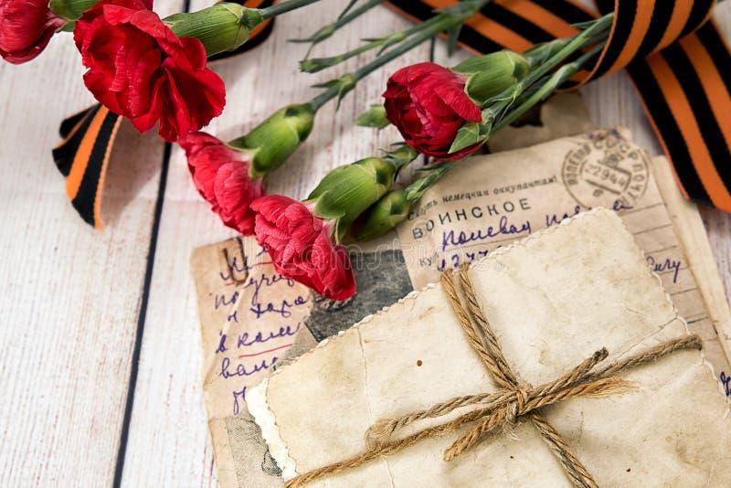 Letra militar, fotos viejas, claveles y la cinta de Gergiev fotos de archivo