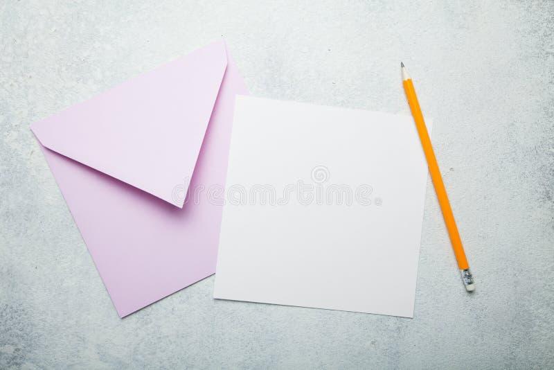 Letra o postal de invitación Un trozo de papel cuadrado vacío con el espacio para el texto, un sobre rosado y un lápiz en un blan fotos de archivo