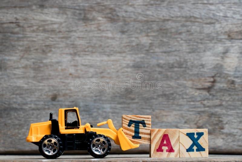 Letra plástica amarilla T del control de la niveladora para terminar impuesto de la palabra sobre el fondo de madera fotos de archivo libres de regalías