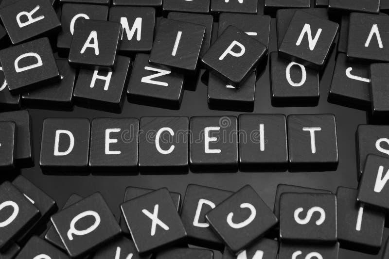 A letra preta telha a soletração da palavra & do x22; deceit& x22; imagens de stock