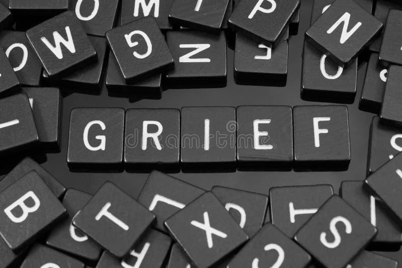 A letra preta telha a soletração da palavra & do x22; grief& x22; foto de stock