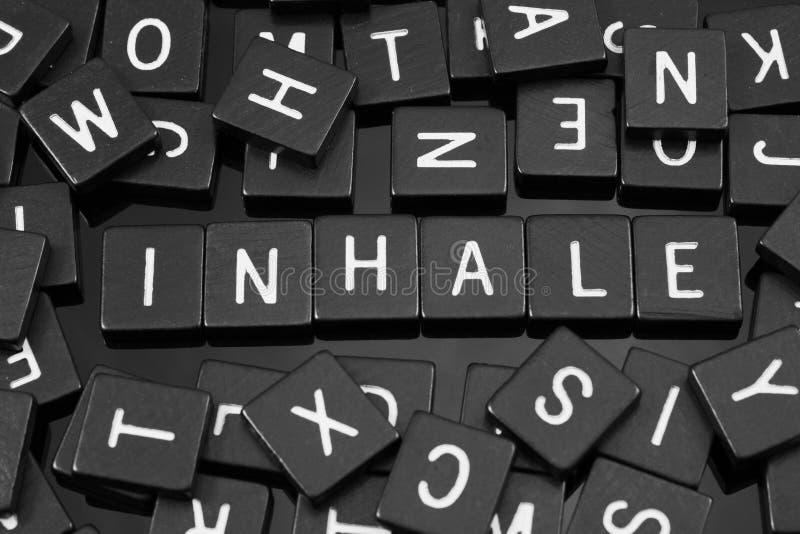 A letra preta telha a soletração da palavra & do x22; inhale& x22; foto de stock