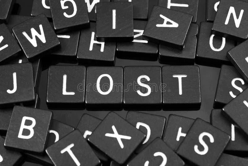A letra preta telha a soletração da palavra & do x22; lost& x22; imagem de stock royalty free