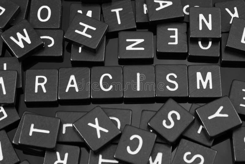 A letra preta telha a soletração da palavra & do x22; racism& x22; fotos de stock royalty free
