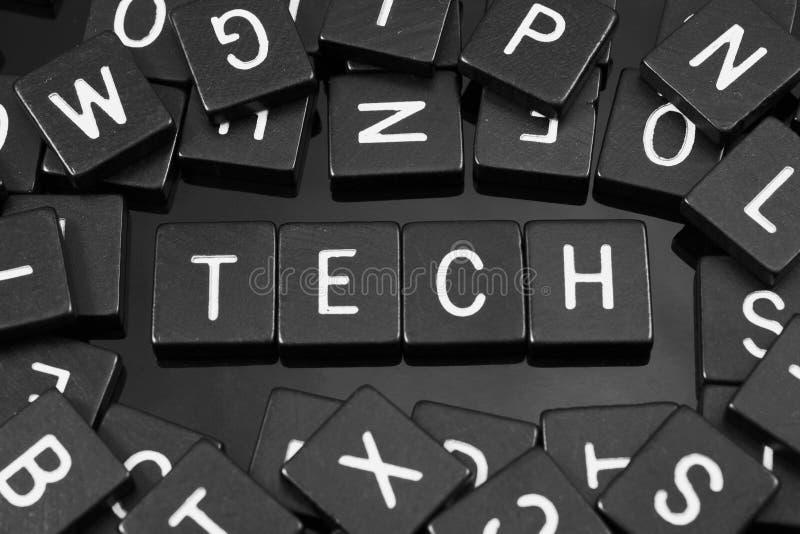 A letra preta telha a soletração da palavra & do x22; tech& x22; foto de stock