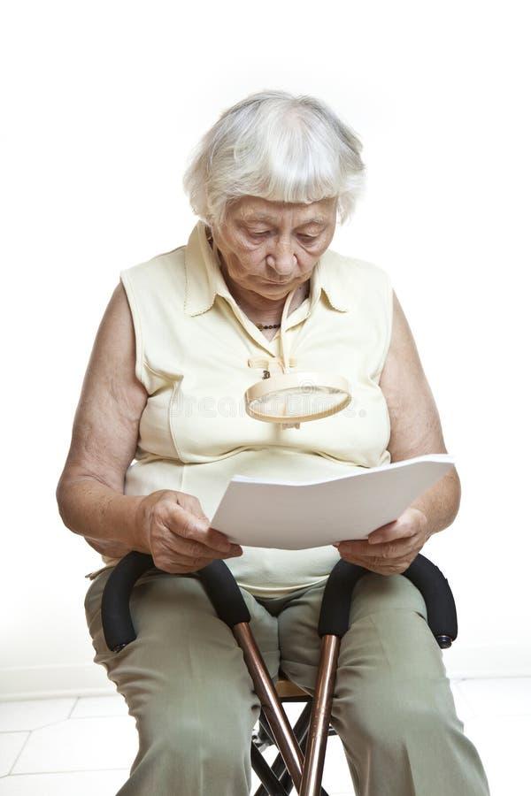 Letra sênior interessada da leitura foto de stock royalty free