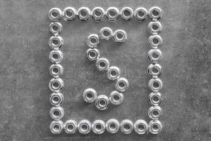 A letra s do alfabeto inglês ou latino alinhou com porcas do metal fotografia de stock royalty free