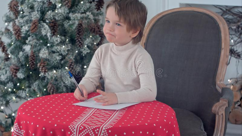 Letra seria de la escritura del niño pequeño a Papá Noel que se sienta en la tabla cerca del árbol de navidad imágenes de archivo libres de regalías
