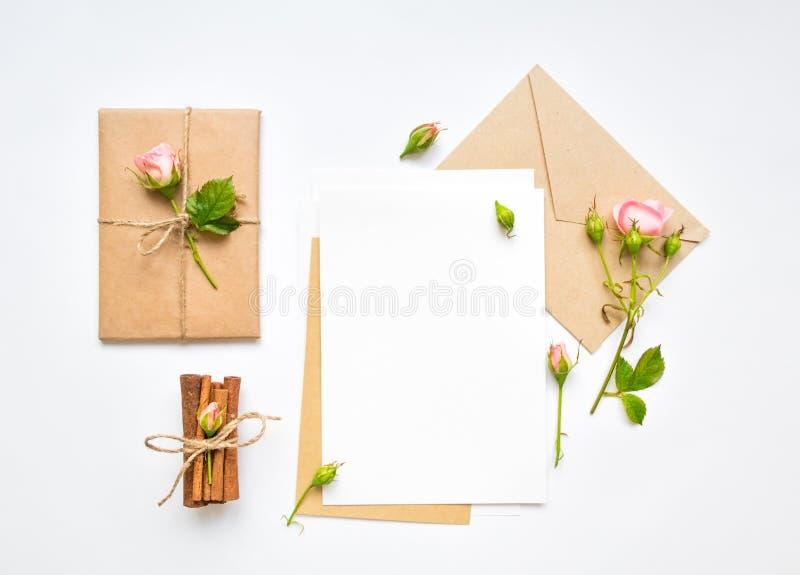 Letra, sobre y regalo en el fondo blanco Tarjetas de la invitación, o letra de amor con las rosas rosadas Concepto del día de fie imagen de archivo libre de regalías