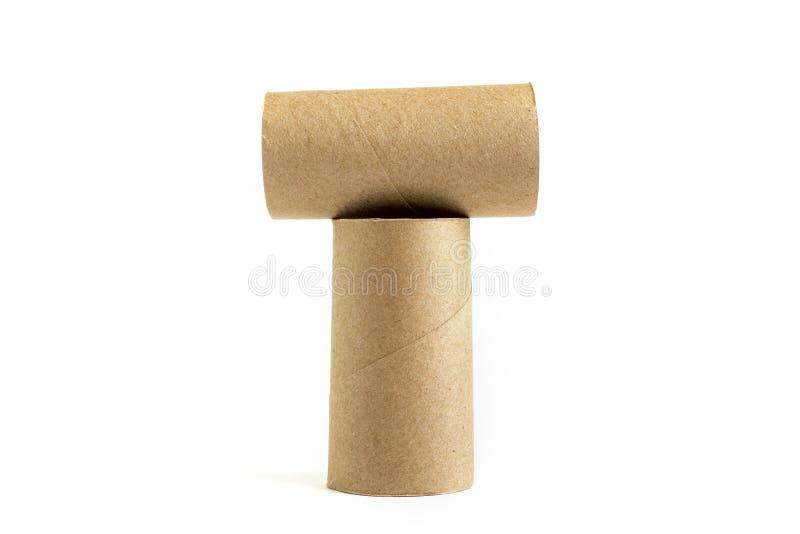 Letra T de uma composição de dois tubos de papel do cartão no fundo branco Close-up de rolos de toalete vazios imagens de stock