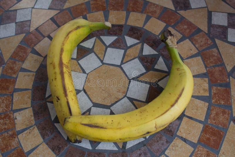 Letra V o C hecha con los plátanos para formar una letra del alfabeto con las frutas fotografía de archivo