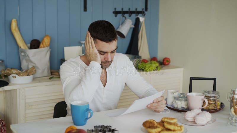 Letra virada da leitura do homem novo com conta por pagar na cozinha em casa imagens de stock royalty free