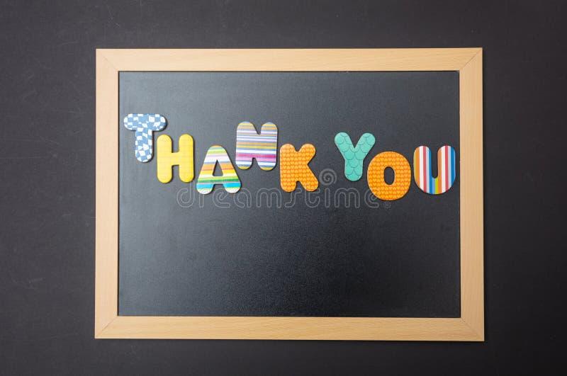 Letras coloridas que forman la palabra para agradecerle en la pizarra con el marco de madera, fondo negro de la pared fotos de archivo libres de regalías