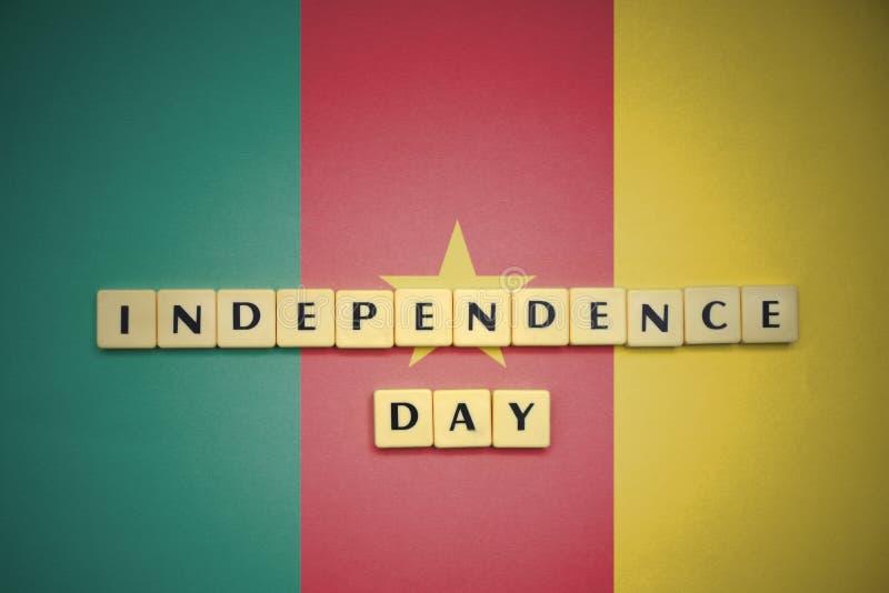 Letras con Día de la Independencia del texto en la bandera nacional del Camerún fotografía de archivo libre de regalías