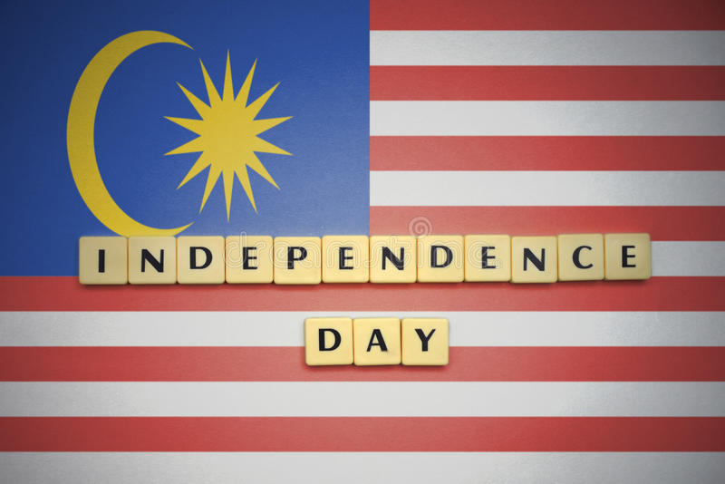 Letras con Día de la Independencia del texto en la bandera nacional de Malasia fotos de archivo libres de regalías