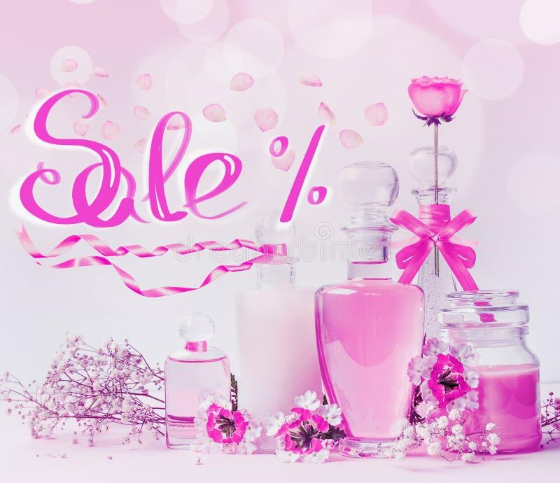 Letras cosméticas del texto de la venta con las botellas del producto de cristal, las cintas rosadas y las flores colocándose en  foto de archivo libre de regalías