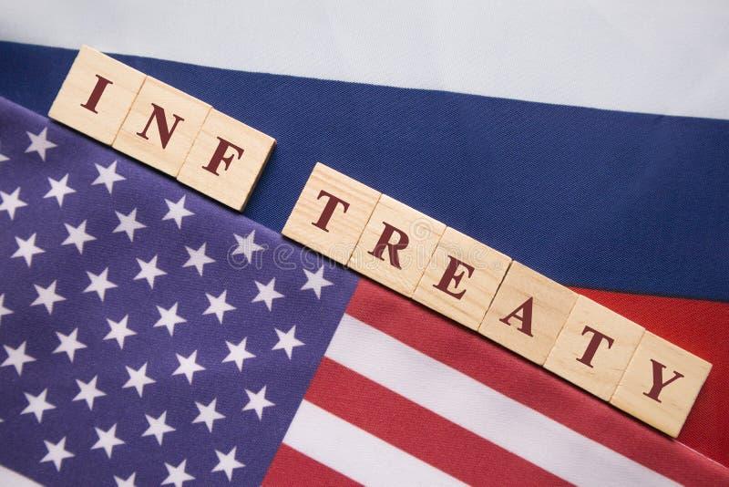 Letras de bloco de madeira escritas do Tratado de INF entre a bandeira dos E.U. e do russo, conceito do tratado de INF assinado p fotos de stock royalty free