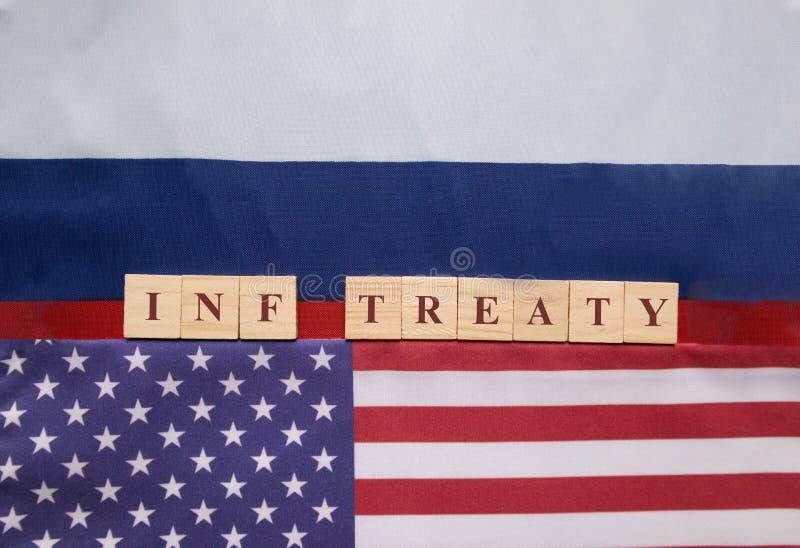 Letras de bloco de madeira escritas do Tratado de INF entre a bandeira dos E.U. e do russo, conceito do tratado de INF assinado p imagens de stock