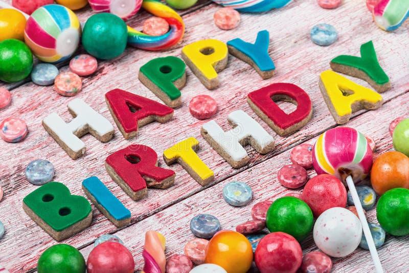 Letras de las galletas del feliz cumpleaños y dulces y caramelos en el th imagenes de archivo