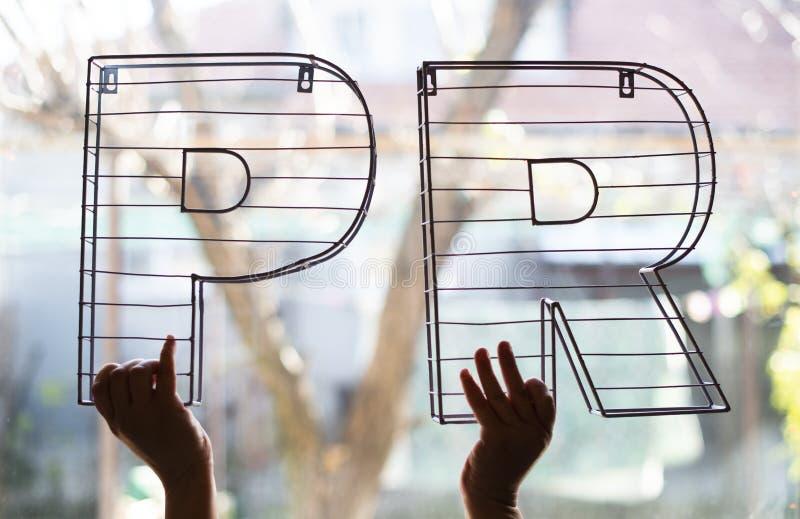 Letras de las relaciones públicas delante de la ventana Concepto del márketing y del negocio fotos de archivo