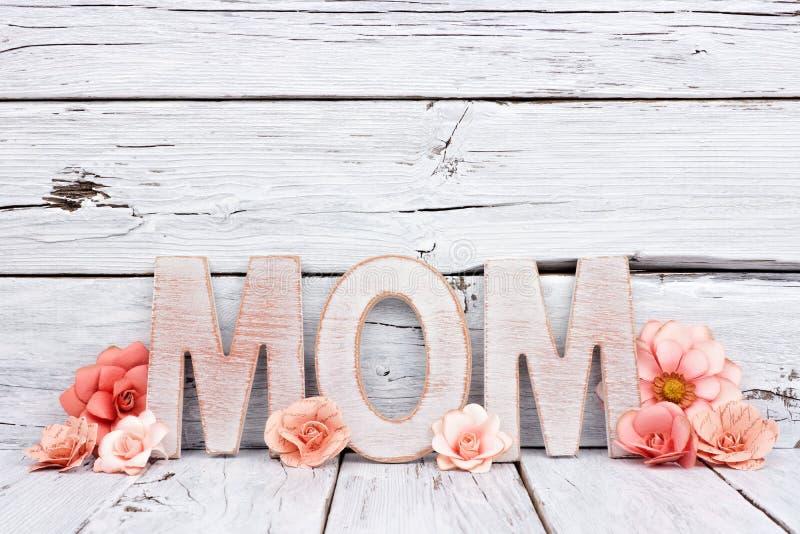 Letras de madeira da MAMÃ com as flores de papel contra a madeira branca foto de stock royalty free
