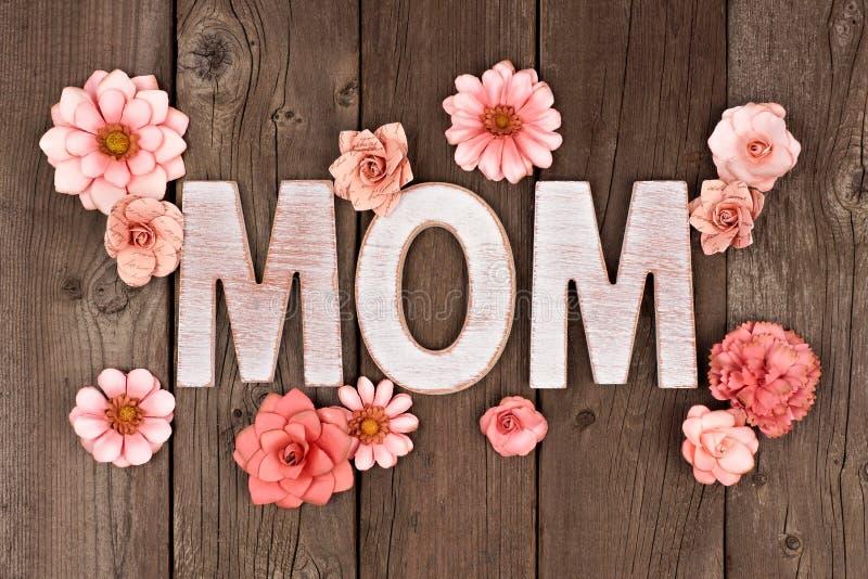 Letras de madeira da MAMÃ com as flores de papel sobre a madeira rústica imagens de stock royalty free