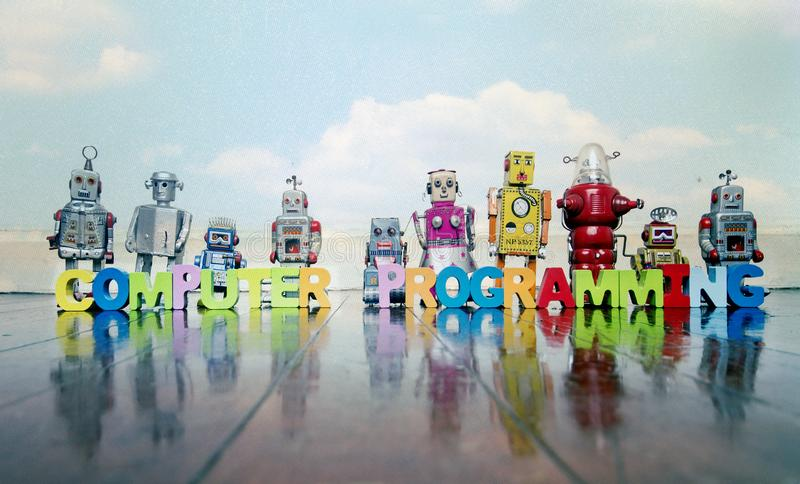 Letras de madera de la PROGRAMACIÓN INFORMÁTICA y juguetes retros del robot foto de archivo libre de regalías