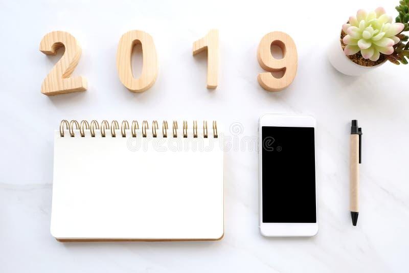 2019 letras de madera, papel en blanco del cuaderno, teléfono elegante blanco con la pantalla en blanco y lápiz en el fondo de má imágenes de archivo libres de regalías