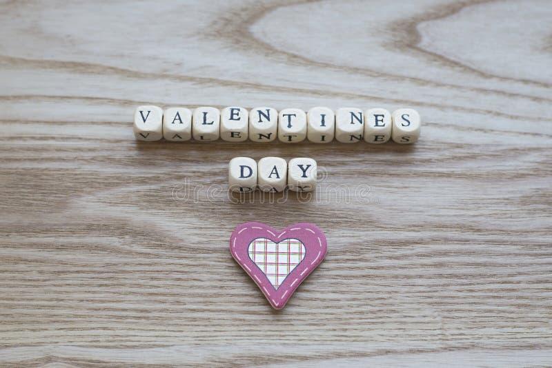 Letras de madera que deletrean día de tarjetas del día de San Valentín en un fondo de madera con un corazón cosido rojo y poner c imagen de archivo libre de regalías