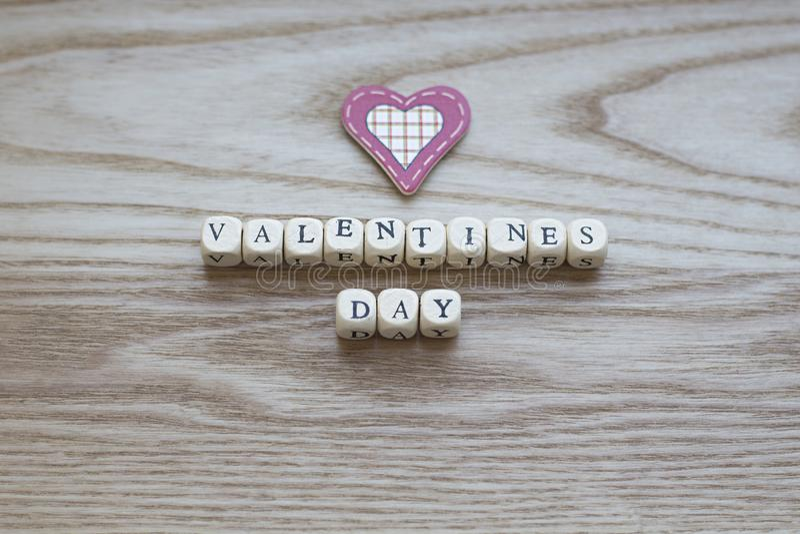 Letras de madera que deletrean día de tarjetas del día de San Valentín en un fondo de madera con un corazón cosido rojo y poner c imagen de archivo