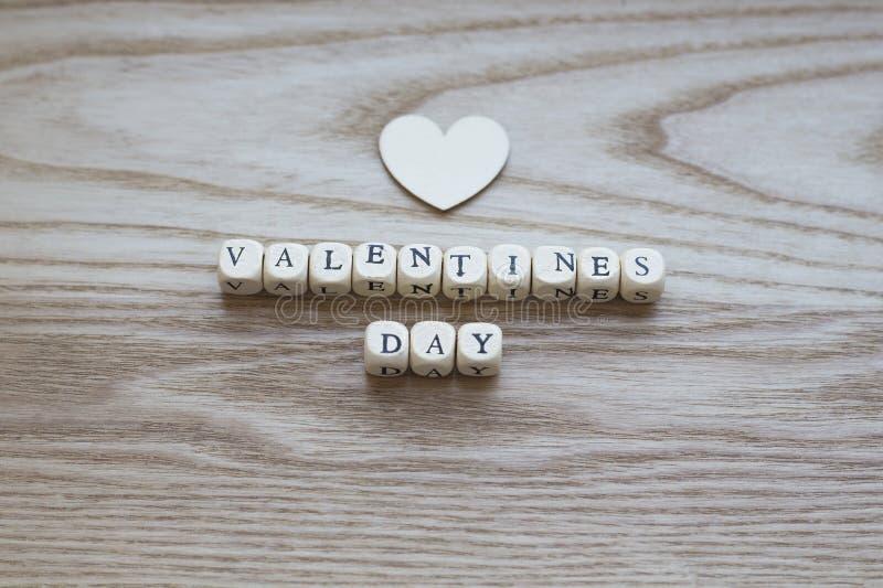 Letras de madera que deletrean día de tarjetas del día de San Valentín en un fondo de madera con un corazón de madera puesto arri foto de archivo libre de regalías