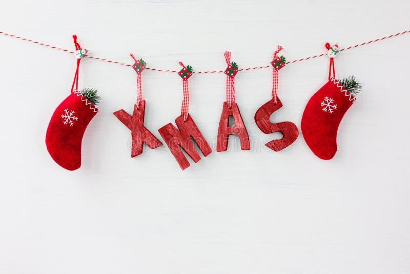 Letras de madera rojas que forman la palabra Navidad y calcetines rojos de la Navidad encendido imagenes de archivo
