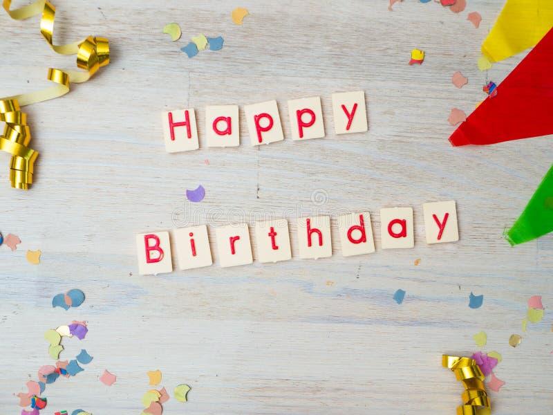 Letras del feliz cumpleaños con la decoración del partido en fondo de madera fotografía de archivo libre de regalías