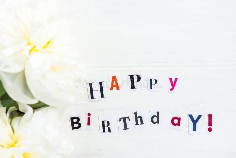 Letras del feliz cumpleaños cortadas de las revistas y de las peonías blancas fotografía de archivo libre de regalías