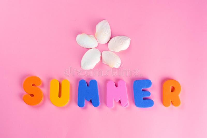 Letras del VERANO de la palabra y cáscara de la concha marina o del mar en fondo rosado Idea original para el diseño del verano E foto de archivo libre de regalías