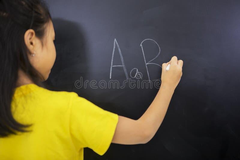 Letras do alfabeto da escrita da menina no quadro-negro fotografia de stock