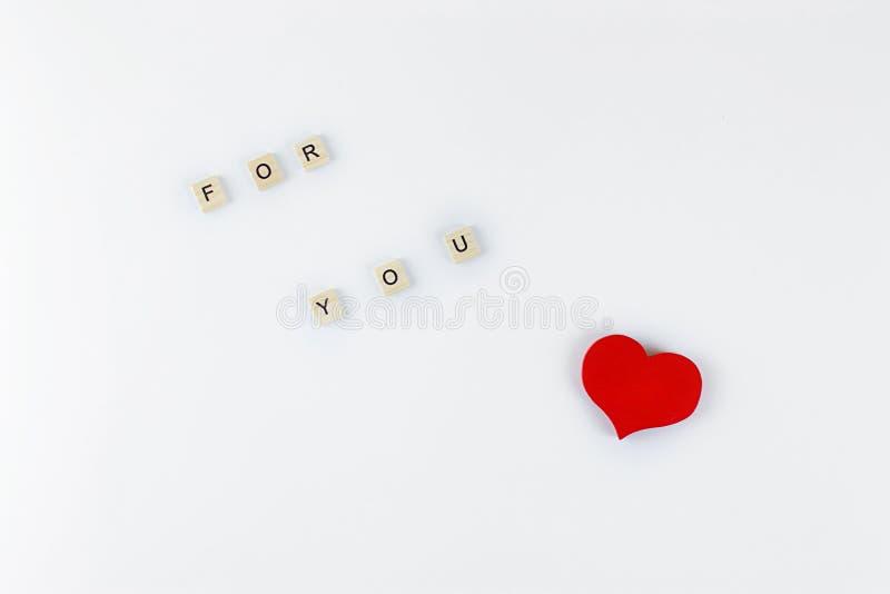 Letras e coração vermelho de madeira em um fundo branco imagens de stock royalty free
