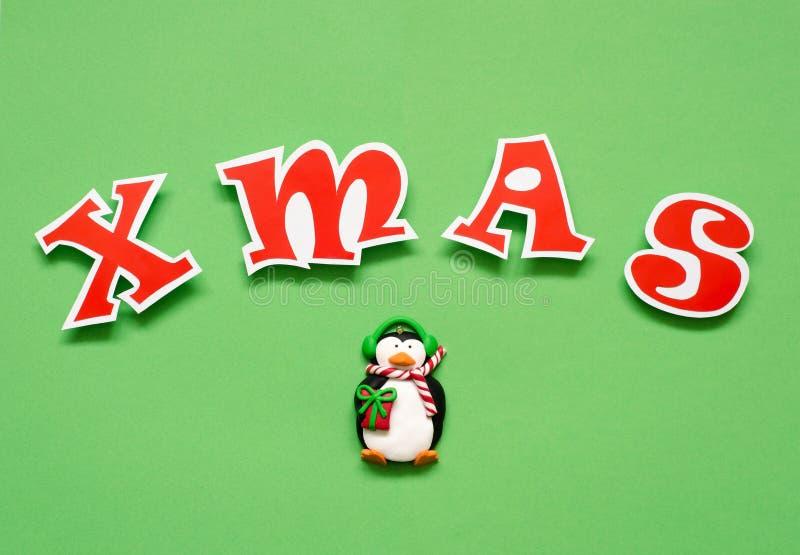 Letras e pinguim de papel vermelhos do brinquedo no fundo verde fotografia de stock