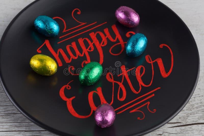 Letras felices de la mano de Pascua escritas en rojo en decoros de la placa negra imagen de archivo
