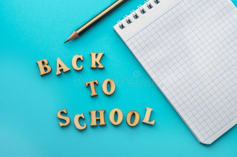 Letras, lápiz y cuaderno en fondo de la turquesa Desde arriba de la inscripción de nuevo a escuela y del lápiz con el cuaderno en foto de archivo libre de regalías