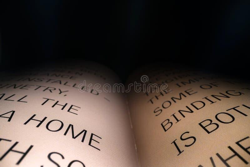 Letras latinas y palabras en un libro abierto con el fondo dramático negro Educación, concepto del conocimiento, espacio para e imagen de archivo