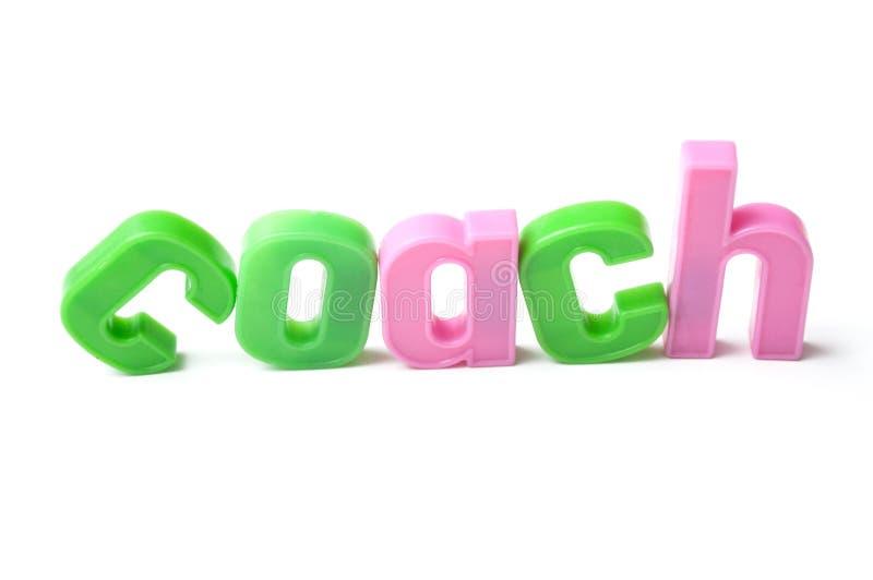 Letras plásticas coloridas no fundo branco - treinador fotografia de stock royalty free