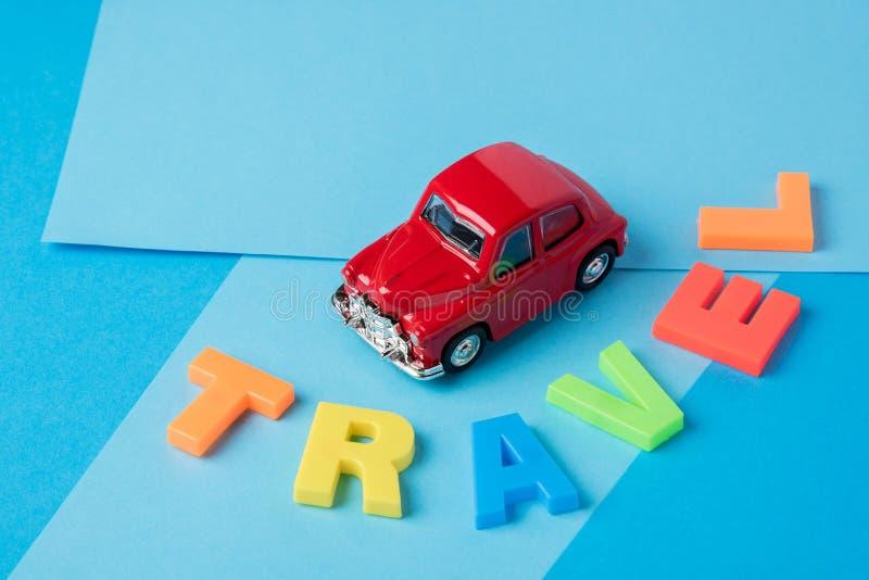 Letras plásticas rojas del viaje del coche y de la inscripción del juguete en un CCB azul fotografía de archivo libre de regalías
