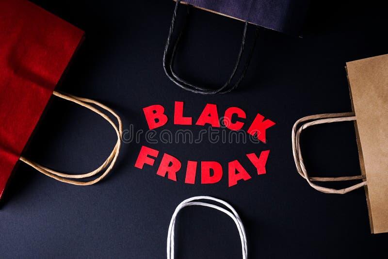 Letras vermelhas Black Friday num fundo preto com sacos kraft coloridos fotos de stock royalty free